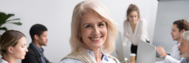 Retrato horizontal de la foto de la empresaria mayor que sonríe mirando la cámara foto de archivo libre de regalías