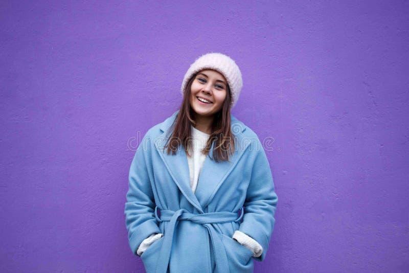 Retrato horizontal de la hembra caucásica agradable con el pelo marrón, la capa casual azul que lleva y el sombrero de lana calie imagenes de archivo