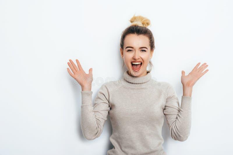 Retrato horizontal de la mujer alegre con la emoción del placer, comiendo el bollo del pelo que lleva en el suéter aislado sobre  fotos de archivo libres de regalías