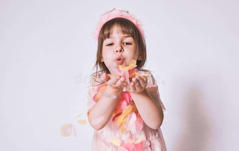 Retrato horizontal de la niña linda que lleva el vestido rosado en Tulle con la corona de la princesa en la cabeza en el fondo bl foto de archivo