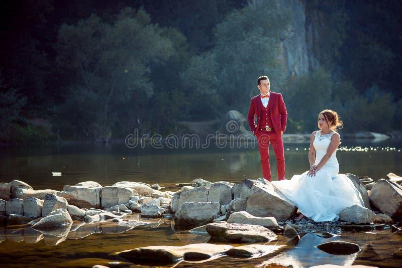Retrato horizontal de los pares felices del recién casado cerca del río La novia principal roja encantadora se está sentando en l fotografía de archivo