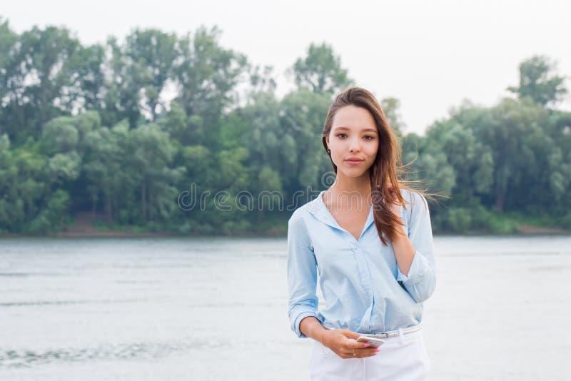 Retrato horizontal de uma mulher atrativa bonita no fundo da margem Moça que olha a câmera e o sorriso fotografia de stock royalty free