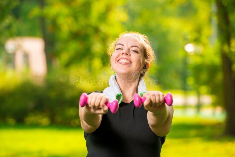 retrato horizontal de uma mulher positiva de sorriso do tamanho com pesos no parque imagens de stock