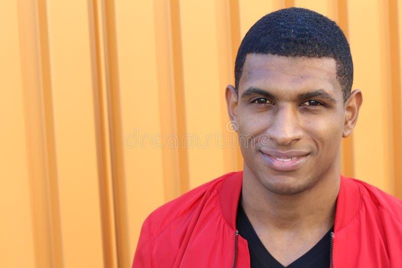 Retrato horizontal de un hombre africano joven hermoso que sonríe en fondo anaranjado foto de archivo
