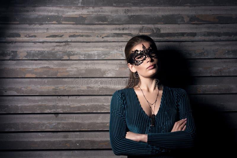 Retrato horizontal de una mujer joven que se coloca en la pared con sus brazos doblados imagen de archivo libre de regalías