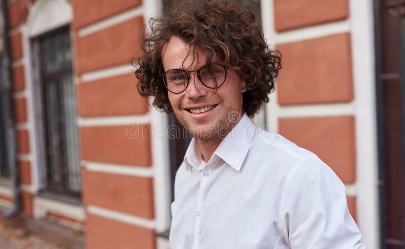 Retrato horizontal del hombre de negocios feliz joven con los vidrios que sonríe y que presenta al aire libre Estudiante masculin foto de archivo