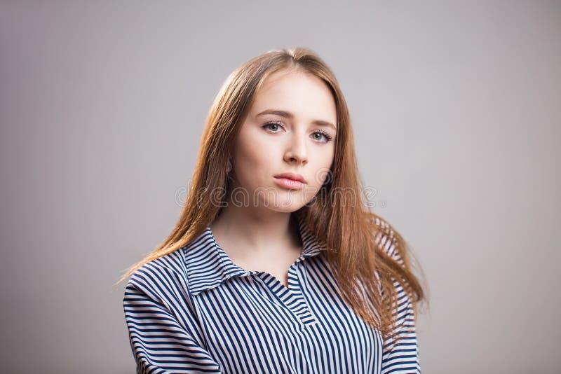Retrato horizontal del primer de la muchacha atractiva del estudiante en fondo gris con el espacio de la copia Mujer joven con be imagen de archivo