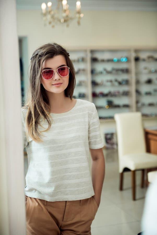 Retrato horizontal do cliente fêmea europeu novo encantador que está na loja do ótico, par à moda de tentativa de imagem de stock