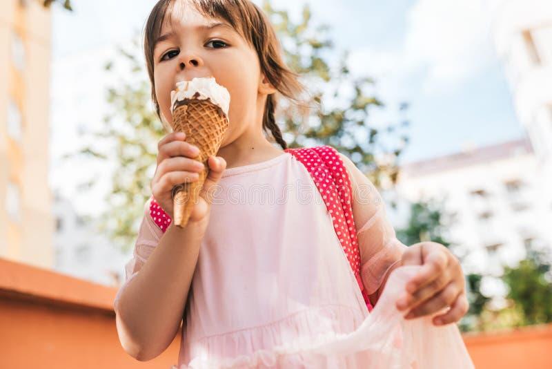 Retrato horizontal do close up da menina bonito que anda ao longo da rua da cidade e que come o gelado exterior A menina feliz da foto de stock royalty free