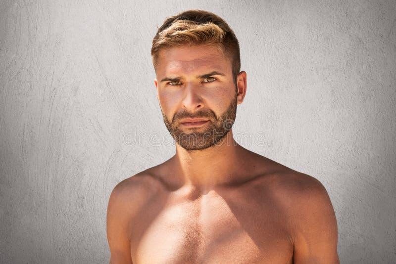 Retrato horizontal do homem não barbeado considerável com olhos escuros, staanding à moda do penteado em topless sobre o fundo ci fotos de stock
