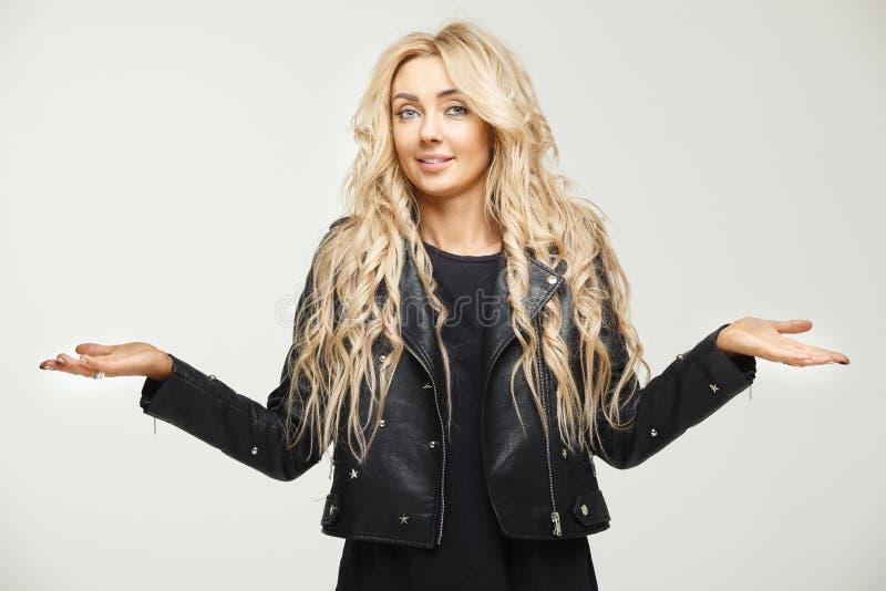 Retrato horizontal femenino desconcertado de un blonde con los hombros de elevación del pelo largo como muestra de la ignorancia  fotos de archivo