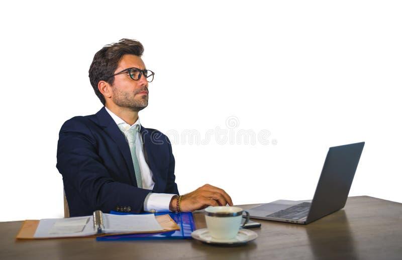 Retrato incorporado do homem de negócio atrativo e eficiente novo que trabalha na mesa do laptop do escritório segura no terno el imagens de stock