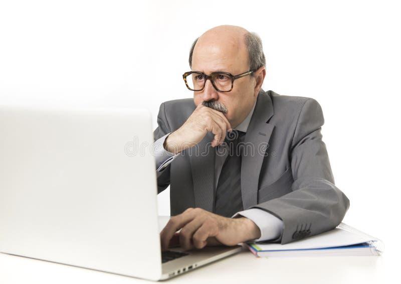 Retrato incorporado 60s calvo sério e homem de negócio autoritário que pensa e que trabalha na mesa de escritório do portátil do  foto de stock royalty free