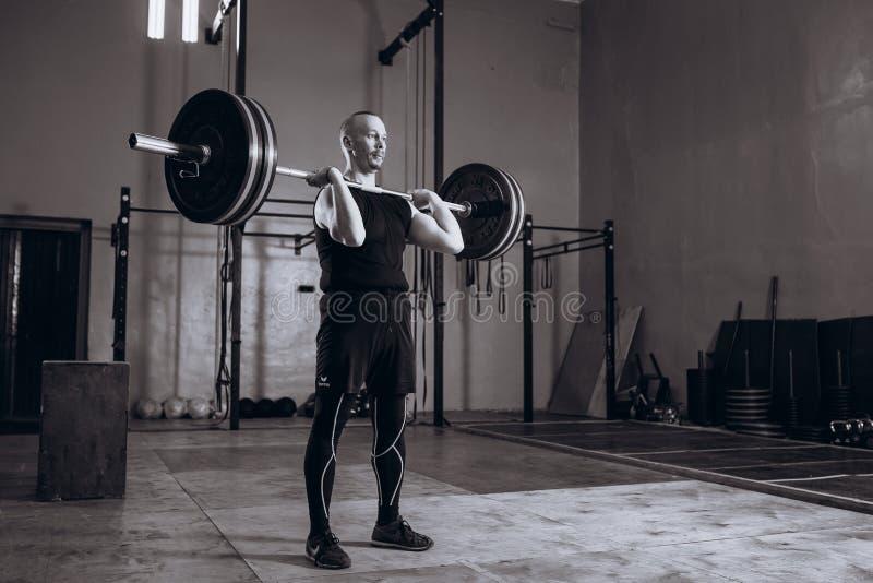 Retrato integral blanco y negro del hombre fuerte que levanta un barbell durante entrenamiento del crossfit en el gimnasio imágenes de archivo libres de regalías