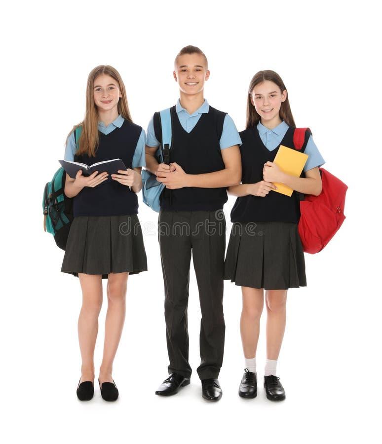 Retrato integral de adolescentes en uniforme escolar en blanco fotografía de archivo libre de regalías