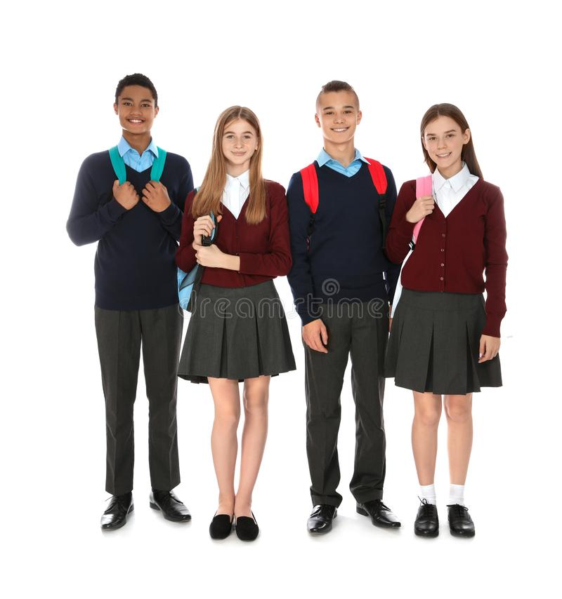 Retrato integral de adolescentes en uniforme escolar con las mochilas foto de archivo