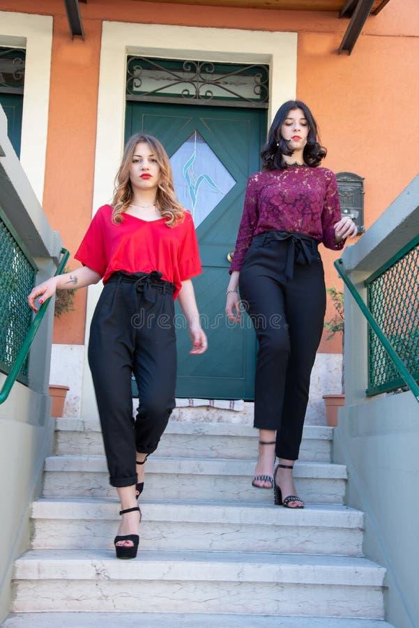 Retrato integral de dos amigos femeninos que caminan abajo de las escaleras en casa imagen de archivo