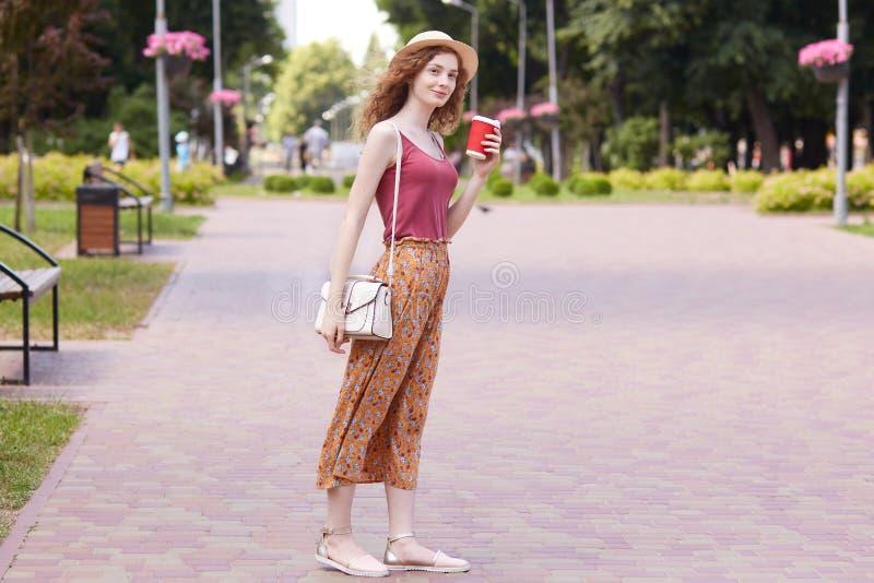Retrato integral de la hembra joven elegante delgada que camina con zona de la reconstrucción en la ciudad nativa, el sombrero qu foto de archivo