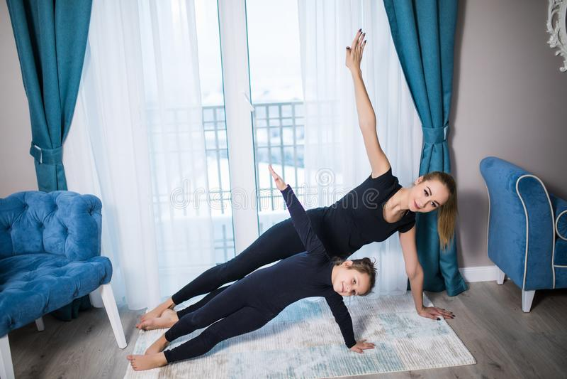 Retrato integral de la madre y de la hija del ajuste que hacen yoga lateral del tablón en la manta en casa foto de archivo libre de regalías