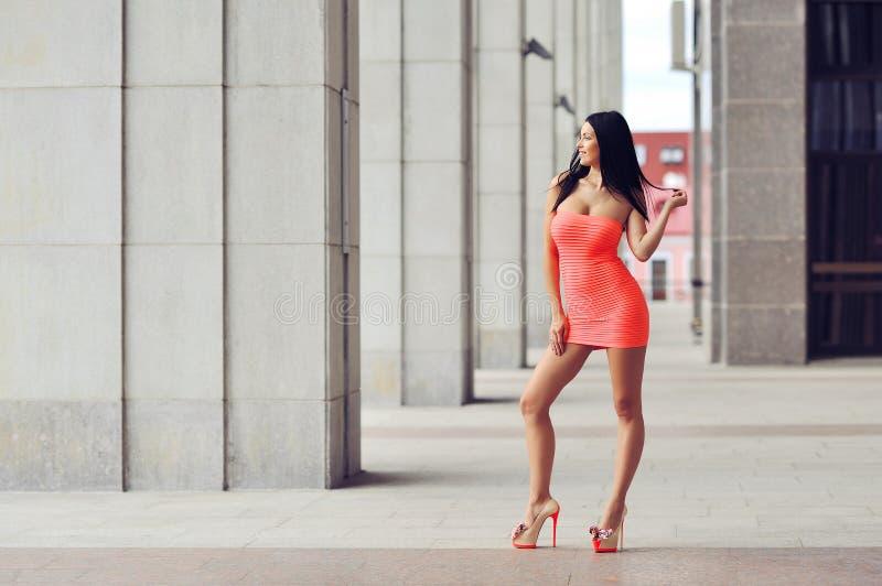 Retrato integral de la moda de la mujer hermosa en la posición roja del vestido foto de archivo
