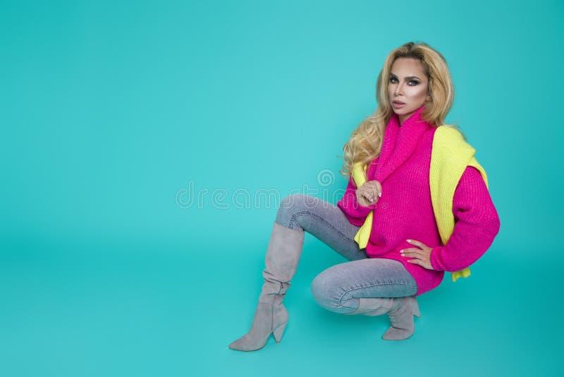 Retrato integral de la muchacha del modelo de moda aislado en fondo azul Mujer rubia elegante de la belleza que presenta en ropa  imagen de archivo libre de regalías