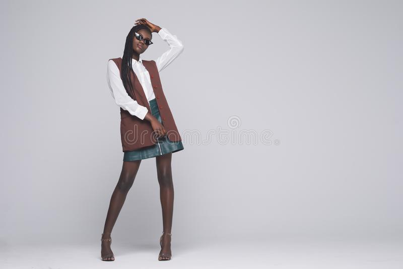 Retrato integral de la muchacha modelo africana de la moda aislado en fondo gris Mujer elegante de la belleza que propone el prod foto de archivo