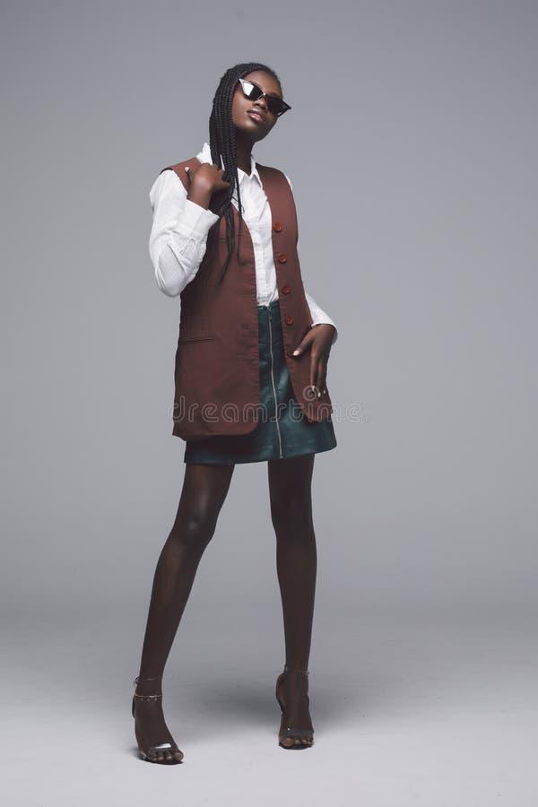 Retrato integral de la muchacha modelo africana de la moda en fondo gris Mujer elegante de la belleza que propone el producto, pu imagenes de archivo