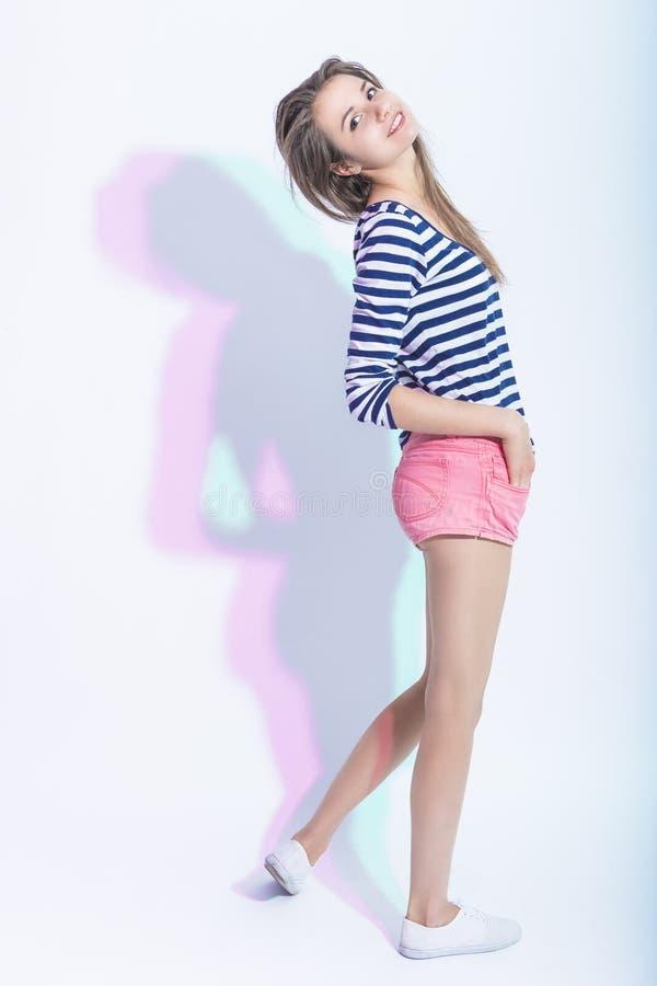 Retrato integral de la muchacha morena caucásica feliz sonriente en camisa rayada y pantalones cortos rosados imagen de archivo libre de regalías