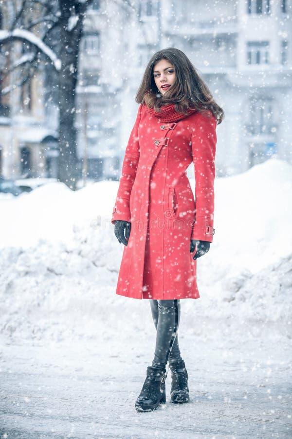 Retrato integral de la mujer extática en la capa roja elegante que se coloca en la calle en día nevoso Foto al aire libre de fema foto de archivo