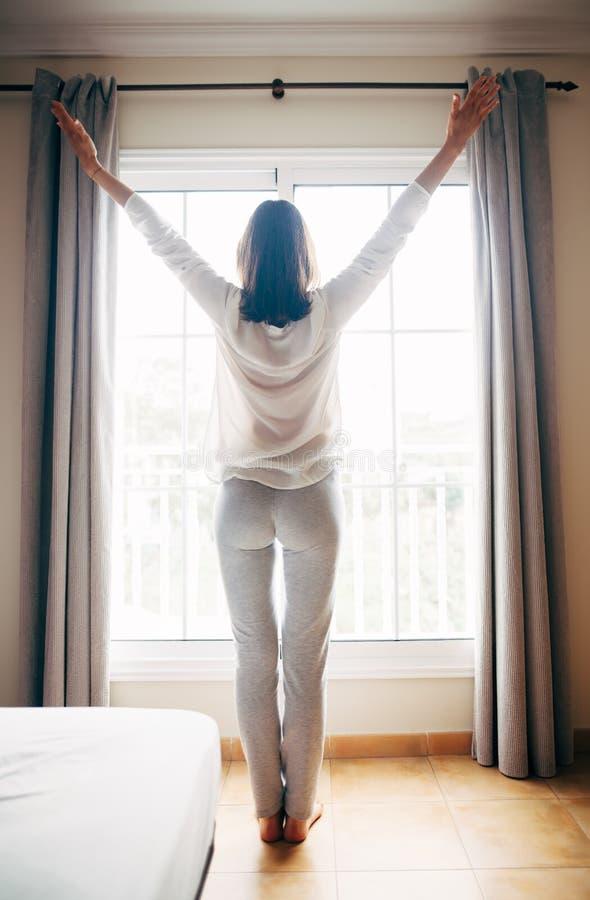 Retrato integral de la mujer feliz que estira cerca de ventana después imagen de archivo libre de regalías