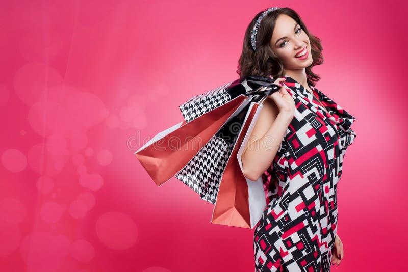Retrato integral de la mujer feliz que sostiene el bolso que hace compras de papel sobre hombro, presentando y sonriendo en la cá imagen de archivo