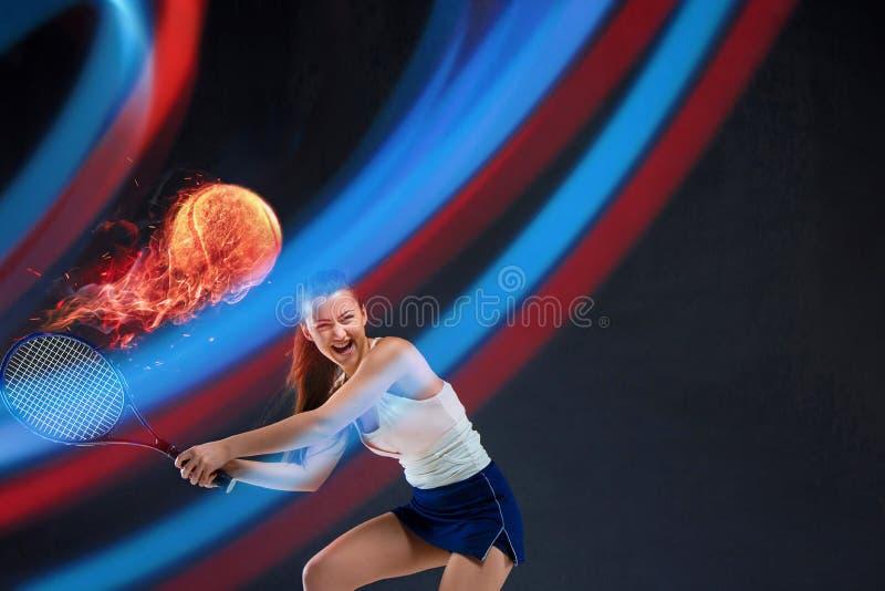 Retrato integral de la mujer joven que juega a tenis en fondo oscuro del estudio fotografía de archivo