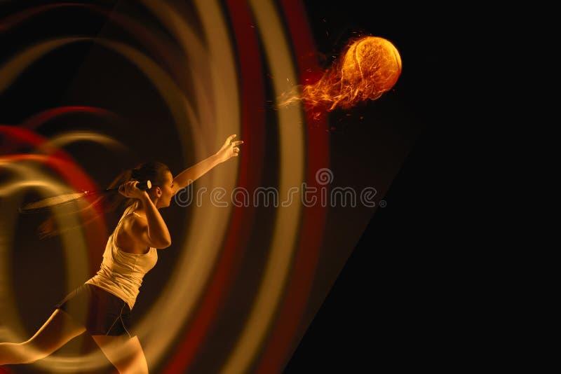 Retrato integral de la mujer joven que juega a tenis en fondo oscuro del estudio fotos de archivo