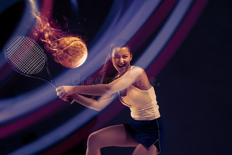Retrato integral de la mujer joven que juega a tenis en fondo oscuro del estudio imagen de archivo