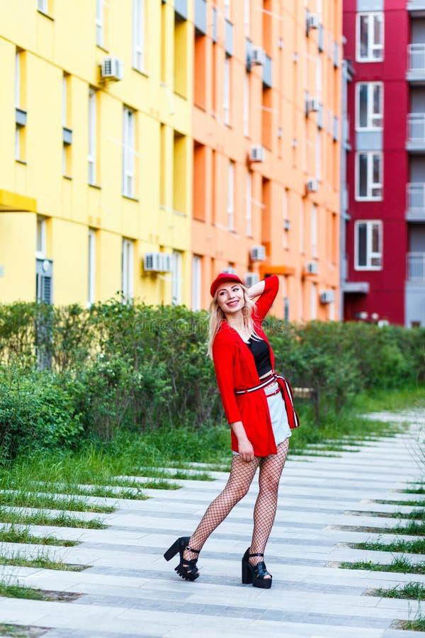 Retrato integral de la mujer joven rubia hermosa del inconformista en blusa roja y el casquillo que presentan cerca de edificios  fotos de archivo