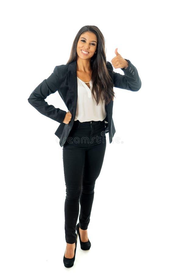 Retrato integral de la mujer latina corporativa latina atractiva que parece excitada y que hace el pulgar encima de la muestra en imagen de archivo libre de regalías