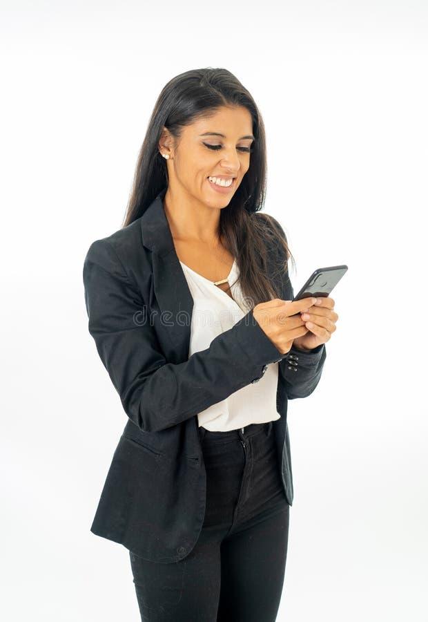 Retrato integral de la mujer latina corporativa latina atractiva que parece feliz y confiada usando el teléfono elegante en éxito fotos de archivo libres de regalías