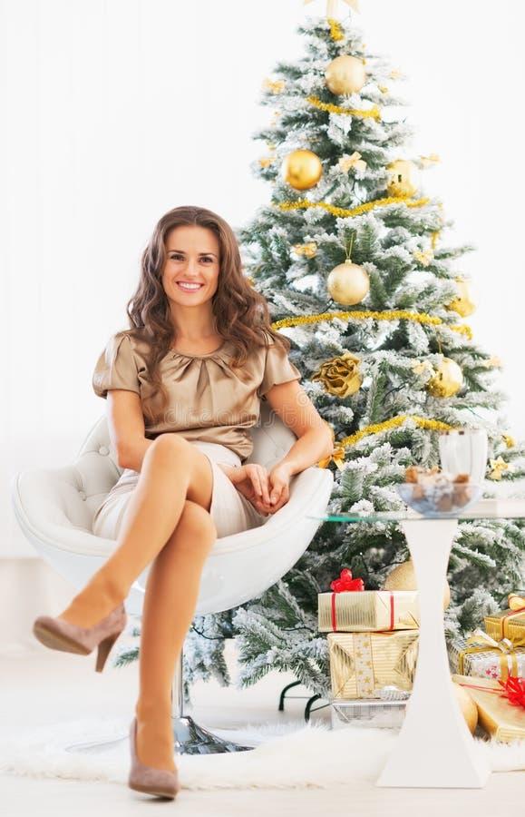 Retrato integral de la mujer que se sienta cerca del árbol de navidad imagenes de archivo