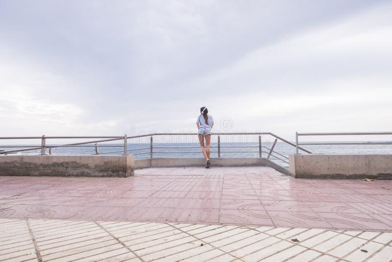 Retrato integral de la situación hermosa de la mujer joven con el azul del océano y del agua en música que escucha del fondo y de imagen de archivo