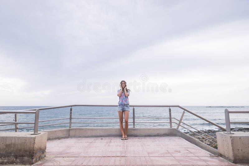 Retrato integral de la situaci?n hermosa de la mujer joven con el azul del oc?ano y del agua en m?sica que escucha del fondo y de fotos de archivo