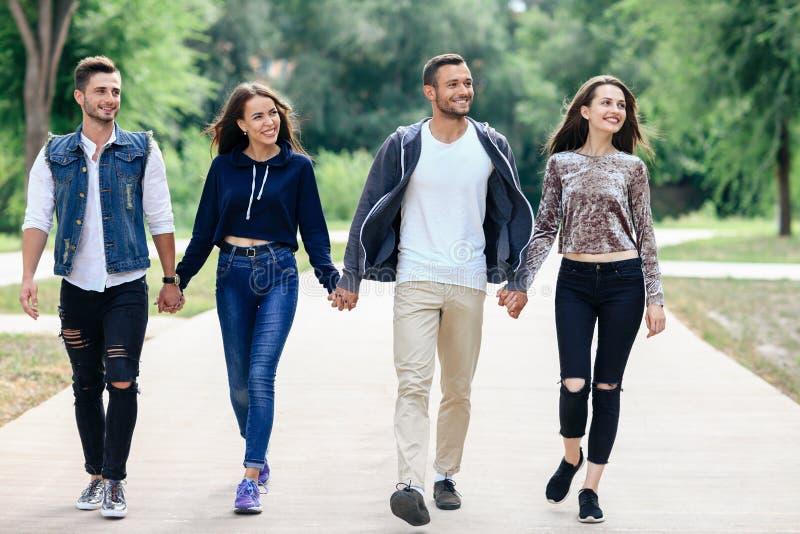 Retrato integral de los amigos jovenes que llevan a cabo las manos que caminan en p foto de archivo