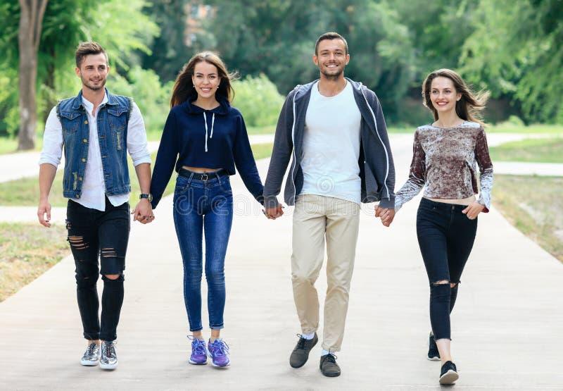 Retrato integral de los amigos jovenes que llevan a cabo las manos que caminan en p imagen de archivo