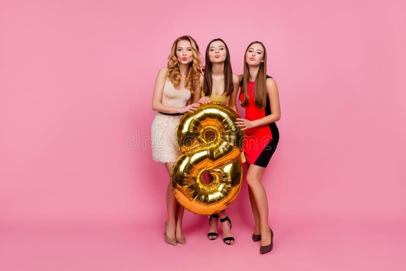 Retrato integral de tres bonitos, muchachas divertidas, beso que sopla foto de archivo libre de regalías