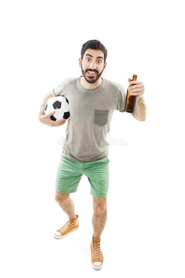 Retrato integral de un aficionado deportivo eufórico que lleva a cabo animar de la botella y del fútbol de cerveza imagen de archivo libre de regalías