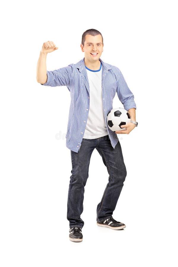 Retrato integral de un aficionado deportivo eufórico que sostiene una bola imagen de archivo libre de regalías