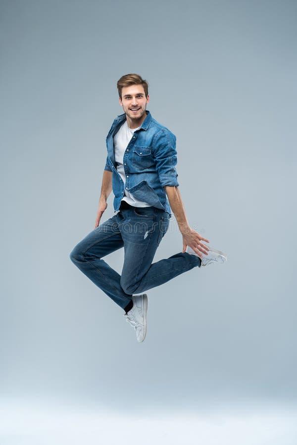 Retrato integral de un beardedman emocionado feliz que salta y que mira la cámara aislada sobre fondo gris foto de archivo