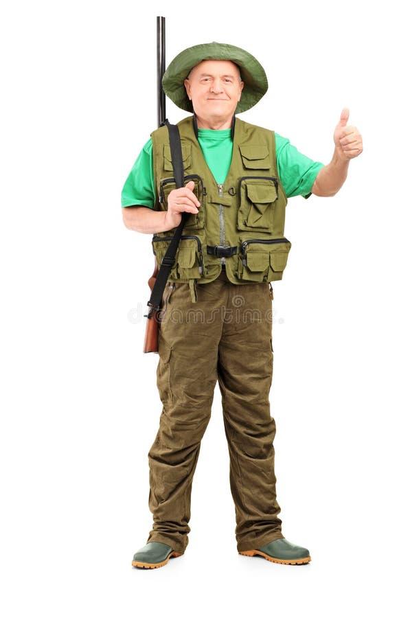 Retrato integral de un cazador masculino con la escopeta que da un thum foto de archivo libre de regalías