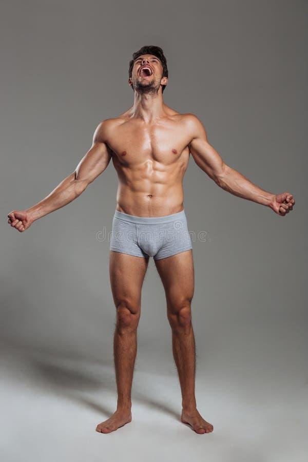 Retrato integral de un grito muscular hermoso del hombre imagen de archivo