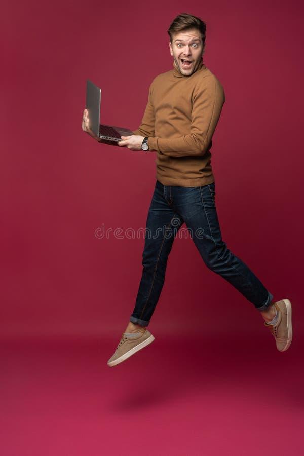 Retrato integral de un hombre joven alegre que lleva la ropa casual aislada sobre el fondo rosado, sosteniendo el ordenador portá imagen de archivo