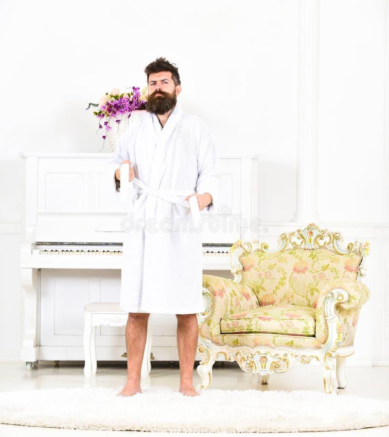 Retrato integral de un hombre joven en una situación de la albornoz aislado en el sitio blanco con el piano Individuo barbudo que fotografía de archivo libre de regalías
